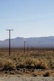 Le linee elettriche passano il deserto Immagini Stock