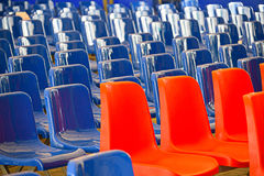 Le linee rette di rosso e del blu hanno colorato i sedili di plastica vuoti immagini stock