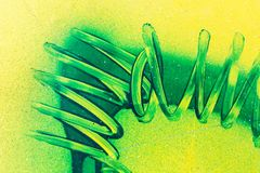 Le linee a spirale di curve verdi della pittura su plastica gialla sorgono Fondo astratto di lerciume del birght immagini stock