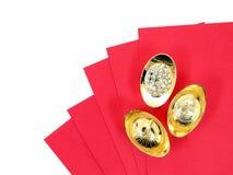 Le lingot chinois antique d'or sur l'enveloppe rouge d'isolement sur les caractères chinois de fond blanc signifient la bénédicti photographie stock