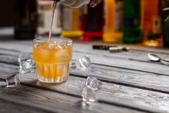 Le liquide orange verse dans le verre photographie stock libre de droits