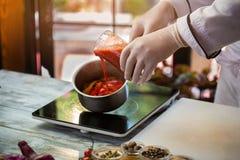 Le liquide rouge verse dans la casserole photos libres de droits
