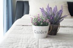 Le lit avec la fleur de lavande et la rose pourpres de rose sur le pot de fleur photographie stock