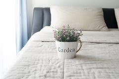Le lit avec la rose de rose sur le pot de fleur Image stock