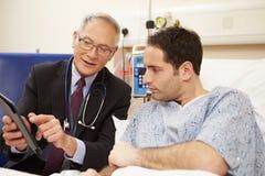 Le lit du patient de docteur Sitting By Male utilisant la Tablette de Digital Image libre de droits