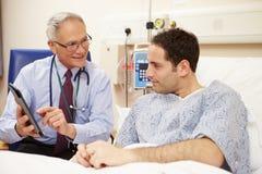 Le lit du patient de docteur Sitting By Male utilisant la Tablette de Digital Image stock