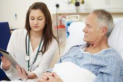 Le lit du patient de docteur Sitting By Male utilisant la Tablette de Digital Photographie stock