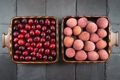 Le litchi et la canneberge portent des fruits dans des deux cuvettes carrées photo stock
