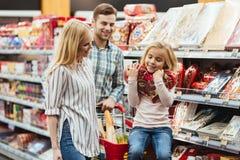 Le liten flickasammanträde och välja godisen med henne föräldrar på supermarket royaltyfri foto
