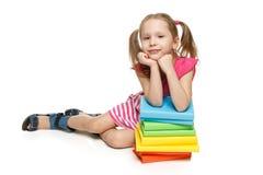 Liten flickasammanträdebenägenheten på bunten av bokar Arkivbild