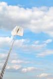 Le livre attaché sur la corde monte dans le ciel bleu-clair Photographie stock libre de droits