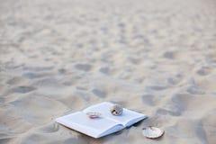 Le livre avec des coquilles de coque sur le sable de mer blanc Photographie stock