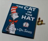 Le livre bien connu le chat dans le chapeau est sur un bureau blanc simple à côté de trois balles image stock