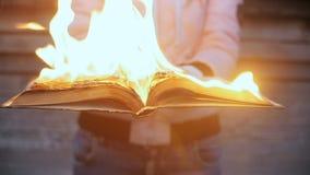 Le livre brûle dans des mains de la fille clips vidéos