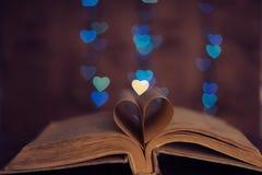 Le livre couvre le coeur de bokeh de coeur et de fond Photo libre de droits