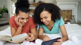 Le livre de lecture de deux amies de métis gai et la tablette drôles d'utilisation parle et a l'amusement se trouvant dans le lit Image libre de droits