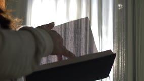 Le livre de lecture de femme près de la fenêtre, le soleil rayonne, mouvement lent banque de vidéos