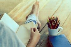 Le livre de lecture sur le plancher en bois avec le livre et la couleur crayonnent - modifiez la tonalité le vintage image stock