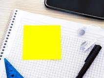 Le livre de mathématiques sur la table de cours et l'étudiant chassent des matériaux avec le papier de note photographie stock