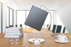 Le livre est comme un globe sur le bureau avec les livres et la tasse de café Images stock