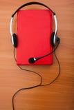 Le livre est rouge avec des écouteurs Photos libres de droits