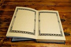 Le livre ouvert aux pages de premiers, fixent à la table en bois brune foncée image stock