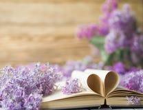 Le livre ouvert sur la table avec des pages aiment le coeur et les fleurs Photos stock