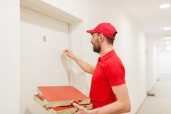Le livreur avec la pizza enferme dans une boîte le frappement sur la porte Photographie stock