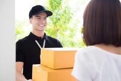 Le livreur fournissent des paquets à une femme photographie stock