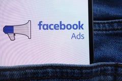 Le logo d'annonces de Facebook montré sur le smartphone caché dans des jeans empochent image libre de droits