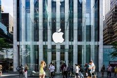 Le logo d'Apple a accroché dans l'entrée en verre de cube à Fifth Avenue célèbre Apple Store à New York Photographie stock libre de droits