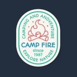 Le logo de camping se composant du feu de camp et le signe explorent la nature Image libre de droits