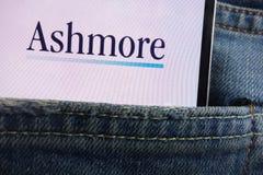 Le logo de groupe d'Ashmore montré sur le smartphone caché dans des jeans empochent photo stock