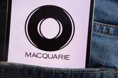Le logo de groupe de Macquarie montré sur le smartphone caché dans des jeans empochent photographie stock libre de droits