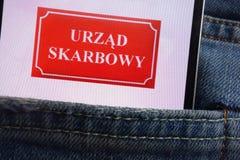 Le logo polonais de bureau d'impôts d'Urzad Skarbowy montré sur le smartphone caché dans des jeans empochent photo stock