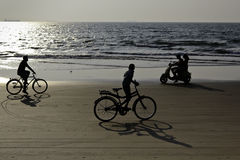 Le long de la côte recyclage et tour sur un scooter sur la plage Images stock