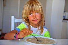 Le long garçon blond de cheveux mangeant l'avoine s'écaille dans la cuisine photos libres de droits