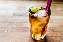 Le Long Island a glacé le cocktail de thé avec la chaux, glace et a servi avec la paille rose Photo libre de droits