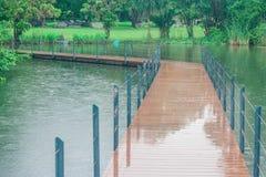 Le long pont en bois croisent plus de le lac en parc public entouré avec naturel vert Photographie stock