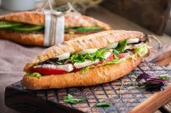 Le long sandwich à baguette avec des tomates de laitue eggs l'oignon et le Mayo Photographie stock libre de droits