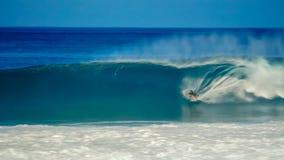 Le long tir d'exposition du surfer atteint un tour de tube la canalisation secrète photos stock