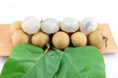 Le Longan frais du plat en bambou, ont des feuilles placées à coté. Image libre de droits