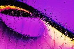 Le luci al neon dietro le gocce di acqua si chiudono su fotografie stock libere da diritti