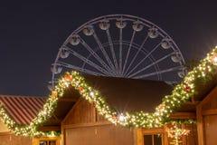 Le luci del mercato di Natale con i ferris spingono dentro i precedenti fotografia stock libera da diritti