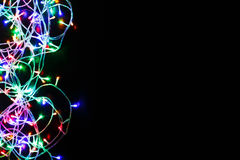 Le luci di Natale rasentano il fondo nero Fotografia Stock