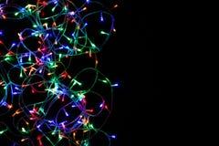 Le luci di Natale rasentano il fondo nero Immagini Stock