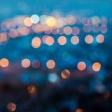 Le luci offuscanti della città sottraggono il bokeh circolare su fondo blu, fotografie stock libere da diritti