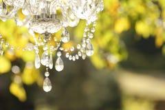 Le lustre en cristal dans la lumière de coucher du soleil sur le fond a brouillé la nature Photos stock