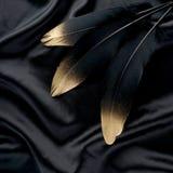 Le luxe a doré la plume d'or de cygne noir d'or sur le fond en soie de tissu images stock