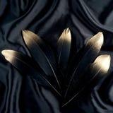 Le luxe a doré la plume d'or de cygne noir d'or sur le fond en soie de tissu photographie stock libre de droits